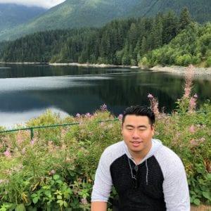 Gerald Yu outdoors next to a lake near mountains